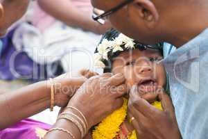Baby girl crying in Hindus ear piercing ceremony