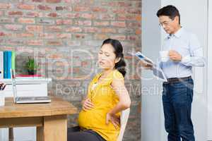 Suffering pregnant woman sitting on chair