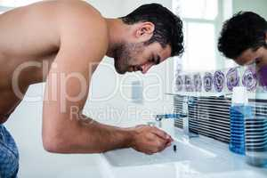 Handsome man washing his face