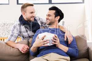 Gay man offering present to his boyfriend