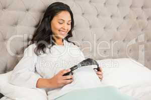 Pregnant brunette putting headphones on belly