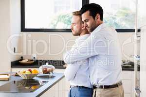 Gay couple with eyes closed hugging