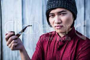 Thoughtful hipster smoking pipe
