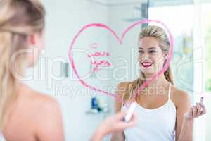 Woman writing on the mirror with lipstick