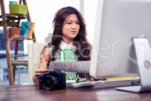 Creative businesswoman holding document and looking at computer