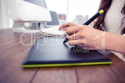 Feminine hands using digital board and computer keyboard