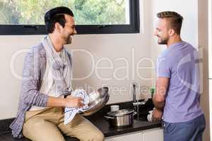 Smiling gay couple washing dishes
