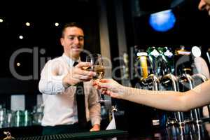 Smiling barman giving glass of white wine to client