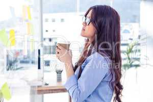 Businesswoman holding disposable cup and looking at wall with no