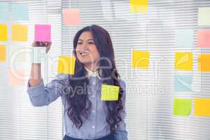 Asian businesswoman using sticky notes on wall
