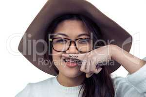 Asian woman with mustache on finger posing for the camera