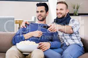 Gay couple watching television with pop corn