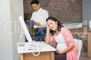 Suffering pregnant woman sitting at desk