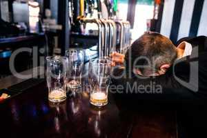 Drunk man with empty glasses