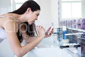 Brunette using smartphone while brushing teeth