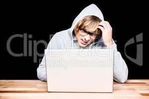 Man in hood jacket hacking a laptop