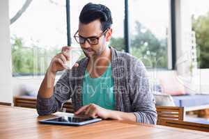 Designer with take-away coffee using tablet