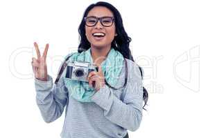 Asian woman holding digital camera and making peace sign with ha