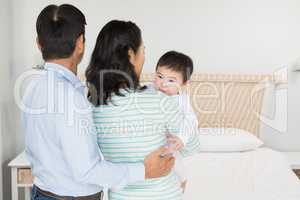 Family with baby daughter in bedroom