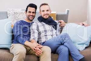 Gay couple holding hands on couch