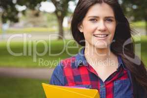 Smiling student holding binder