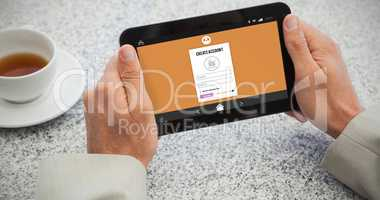 Composite image of businessman holding small tablet at table