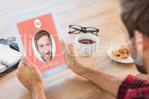 Composite image of rear view of man using tablet on wooden table