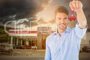 Composite image of handsome young man showing new house key