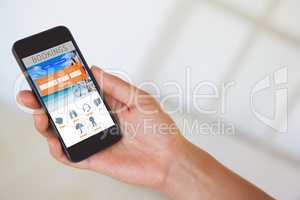 Composite image of womans hand holding black smartphone