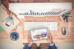 Composite image of businessman holding digital tablet while sitt