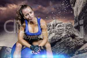 Composite image of sporty woman sitting on exercise ball