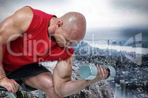 Composite image of bald man exercising with dumbbells while sitt