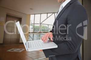Composite image of businessman holding laptop