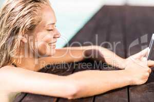 Blonde leaning on pools edge and using smartphone