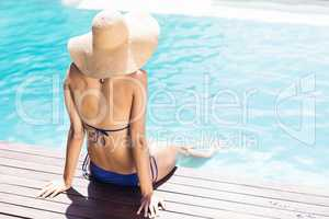 Woman with hat sitting on pools edge