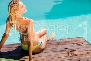 Blonde sitting on pools edge