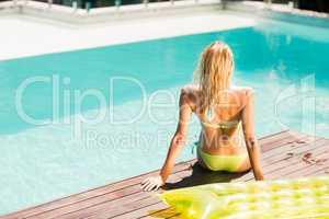 Peaceful blonde sitting on pools edge