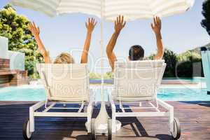 Rear view of couple raising hands and lying on deck chairs