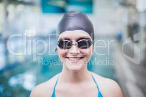 Pretty woman wearing swim cap and swimming goggles