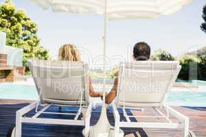 Rear view of couple on deck chairs