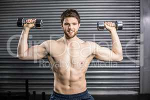 Front view of smiling man lifting weight