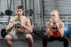 Couple lifting dumbbells together
