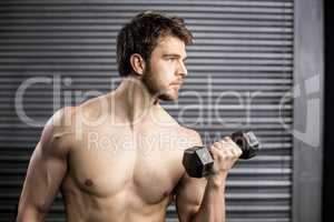 Side view of serious man lifting weight