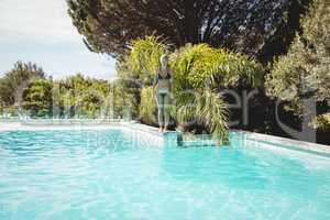 Fit woman standing on pools edge