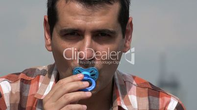 Adult Man Using Baby Pacifier
