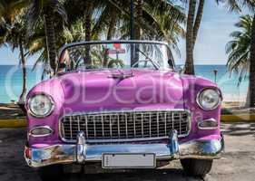 Pink Oldtimer parkt am Strand in Kuba