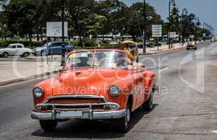 Orangener Oldtimer auf dem Malecon in Kuba Havanna