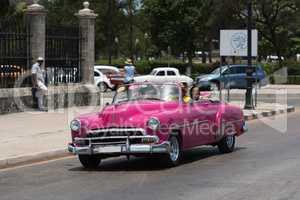 Pink Cabriolet Oldtimer fährt auf dem Malecon in Kuba Havanna