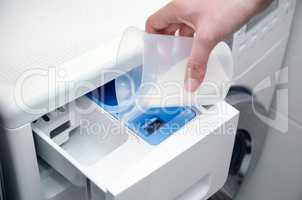 Woman hand pouring washing powder into the washing machine