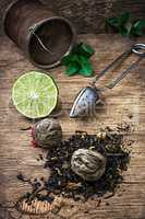tea brew with lime and mint on wooden background